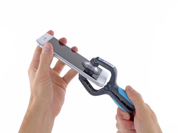 با یک دست بخش فوقانی آیفون را نگه دارید و با دست دیگرتان دستگیره قاب کش را با فشار جمع کنید تا قاب آیفون 6 پلاس تعمیری باز شود.