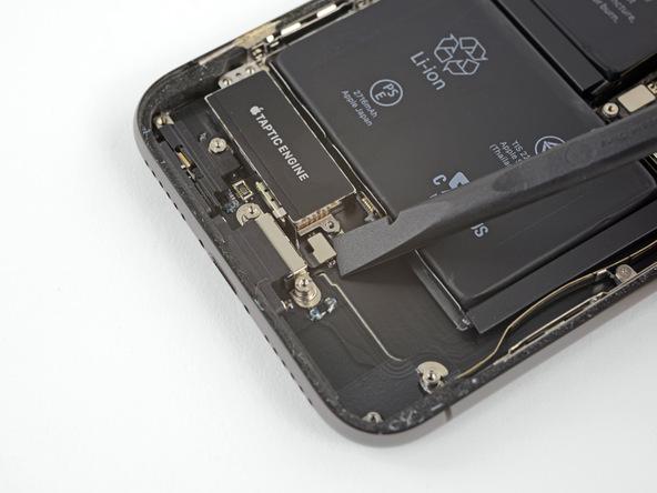 کانکتور موتور تپتیک آیفون ایکس (iPhone X) تعمیری را با نوک اسپاتول از روی برد گوشی آزاد کنید.
