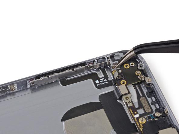 براکت پشت دکمه سایلنت آیفون 6 را با نوک پنس گرفته و به سمت عقب بکشید تا از لبه قاب گوشی آزاد شود.