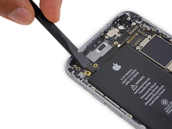 نوک اسپاتول را در لبه فوقانی کانکتور دکمه ولوم آیفون 6S تعمیری قرار داده و آن را از روی برد گوشی باز کنید.
