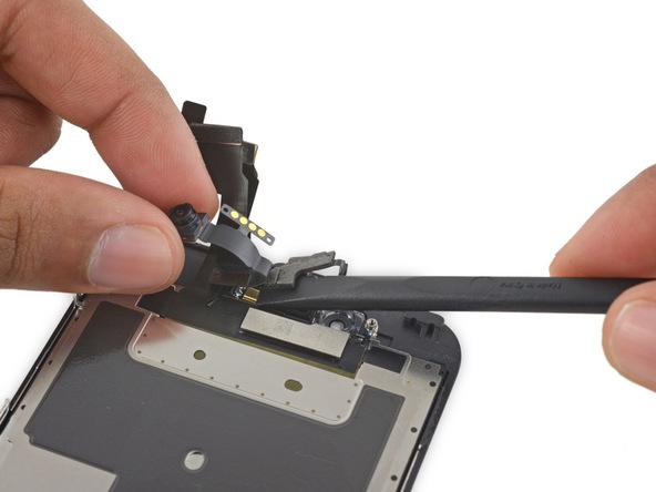 نوک اسپاتول را مثل عکس در زیر کابل دوربین سلفی و سنسور مجاورت آیفون 6 اس تعمیری قرار دهید و آن را به سمت بالا هول دهید تا به میکروفون آیفون دسترسی یابید.