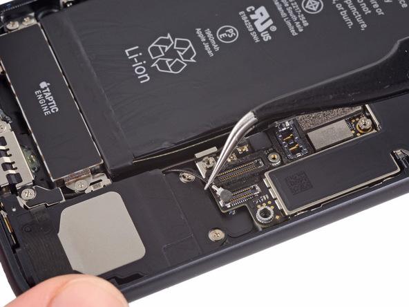 با استفاده از نوک پنس دو کابل آنتن آیفون 7 را گرفته و آن ها را از مسیر برد دستگاه خارج کنید.