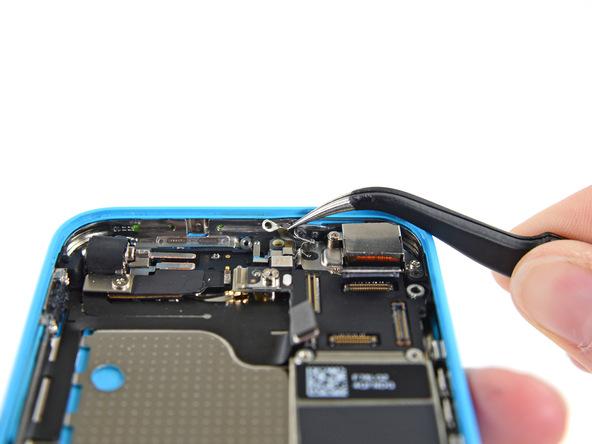 با پنس گیره یا کلیپس اتصال به زمین لاجیک برد آیفون 5c تعمیری را از لبه فوقانی قاب پشت گوشی جدا کنید.