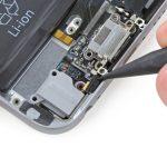 نوک اسپاتول را پشت میکروفون طلایی رنگ لبه زیرین درب پشت آیفون 6 قرار داده و آن را به سمت جلو هول دهید تا از قاب گوشی آزاد شود.