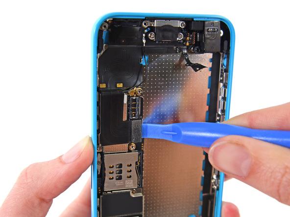 با نوک قاب باز کن کانکتور سوکت شارژ یا همان لایتنینگ پورت آیفون 5C تعمیری را از روی برد گوشی آزاد کنید.
