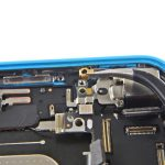 کنتکت طلایی رنگ گوشه لنز دوربین آیفون 5C تعمیری را با پنس از قاب پشت گوشی جدا کنید.