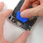 نوک پیک را در راستای عرضی در زیر سیم سوکت شارژ آیفون تعمیری حرکت دهید تا مجموعه سوکت شارژ و جک هدفون آیفون کاملا از روی درب پشت گوشی قابل جداسازی شوند.