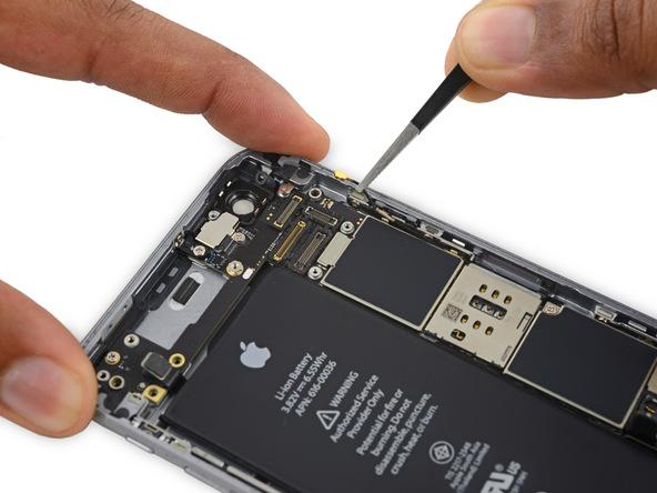 سیم آنتن فوقانی آیفون 6 اس با چند گیره به لبه سمت راست درب پشت گوشی متصل است. با نوک پنس بخش فوقانی سیم مذکور را گرفته