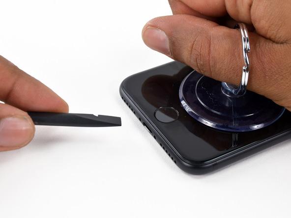 آیفون 7 تعمیری را روی میز کار قرار دهید و ساکشن کاپ را به سمت بالا بکشید تا شکاف کوچکی مابین دو پنل گوشی در لبه زیرین آن ایجاد شود. به محض مشاهده این شکاف، پیک یا نوک پهن اسپاتول را در آن فرو کنید. برای ساده تر شدن کار میتوانید در ابتدا پیک را در شکاف مذکور فرو کنید و کمی آن را به صورت افقی در شکاف حرکت دهید. سپس ساکشن کاپ را به سمت بالا کشیده و این بار نوک اسپاتول را به درون شکاف فرو ببرید.