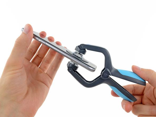 آیفون تعمیری را با دست صاف نگه دارید و با دست دیگرتان دستگیره قاب کش را جمع کنید تا قاب گوشی کاملا باز شود.