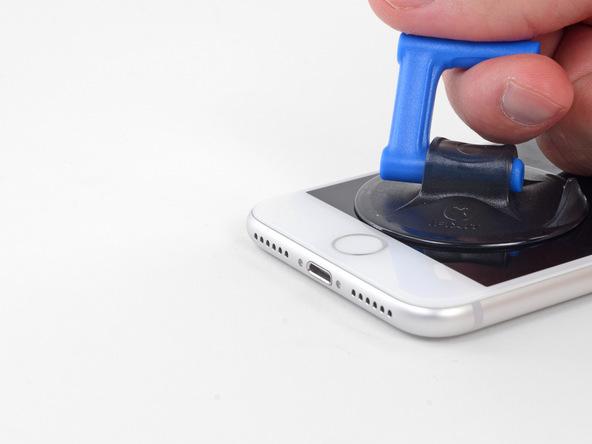 ساکشن کاپ را با انگشت گرفته و به سمت بالا بکشید. سعی کنید تمرکز نیروی کششی روی لبه زیرین قاب گوشی معطوف باشد. به تدریج شدت نیروی کششی را افزایش دید تا شکاف باریکی روی لبه زیرین قاب آیفون 8 تعمیری ایجاد شود. به محض اینکه شکافی روی لب زیرین قاب آیفون 8 ایجاد شد، نوک پیک را به داخل آن فرو ببرید.