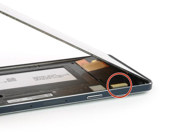 در همان حالتی که ال سی دی گوشی را با زاویه 45 الی 60 درجه نگه داشتهاید، با استفاده از یک اسپاتول کانکتور ال سی دی را از گوشه سمت راست و بالای بدنه گوشی باز کنید.