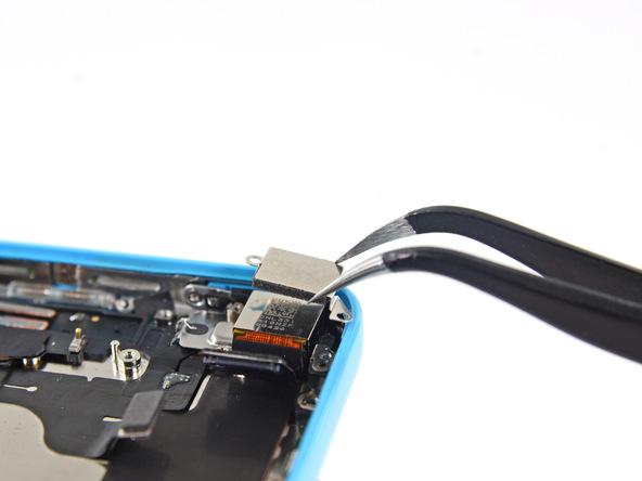 براکت لنز دوربین اصلی آیفون 5c تعمیری را با پنس از قاب پشت گوشی جدا کنید.