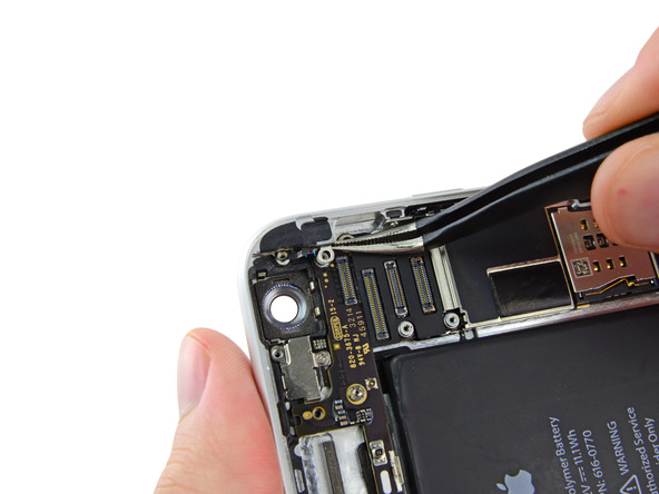با نوک پنس کلیپس فلزی آنتن آیفون 6 پلاس تعمیری را از روی برد گوشی جدا کنید.