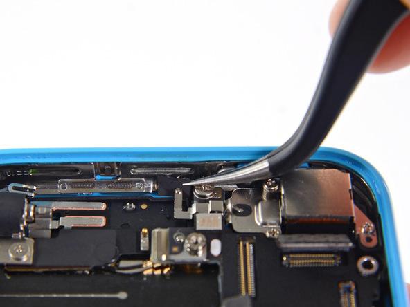 روی کلیپس اتصال به زمین یا پایه آیفون 5C که در گوشه درب پشت آن (کنار لنز دوربین اصلی) واقع شده یک چسب کوچک قرار دارد. این چسب را با پنس گرفته و از درب پشت آیفون جدا نمایید.