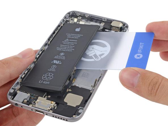 یک قاب باز کن کارتی را به آرامی از سمت راست به زیر باتری آیفون 6 تعمیری فرو برده و آن را از روی درب پشت گوشی بلند کنید.