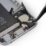 با نوک پنس کاوری که در گوشه سمت چپ و پایین اسپیکر آیفون 6 اس و روی براکت آنتن وای فای آن نصب شده را باز کنید.