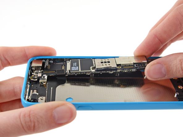 لبه زیرین برد آیفون 5C را به آرامی با انگشت گرفته و از روی درب پشت گوشی بلند کنید.