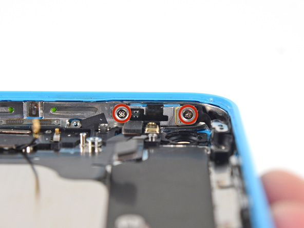 دو پیچ 1.4 میلیمتری نگهدارنده براکت دکمه پاور آیفون 5c که در عکس با رنگ قرمز مشخص شدهاند را از لبه فوقانی قاب گوشی باز کنید.