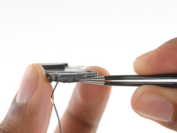 چسب نگهدارندهای که در لبه زیرین اسپیکر آیفون 6 اس چسبانده شده و کابل آنتن گوشی توسط آن نگه داشته میشود را با پنس باز کنید.