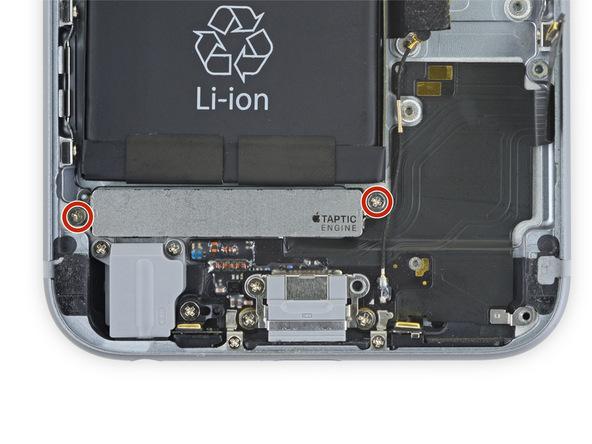 دو پیچ 1.5 میلیمتری که در عکس با رنگ قرمز مشخص شدهاند را باز کنید. این دو پیچ نگهدارنده موتور تپتیک آیفون 6S هستند.