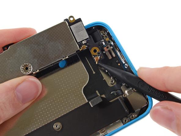 کانکتور سیم آنتی که منجر شده لبه فوقانی برد آیفون 5C تعمیری به درب پشت گوشی متصل شود را با نوک اسپاتول آزاد کنید.