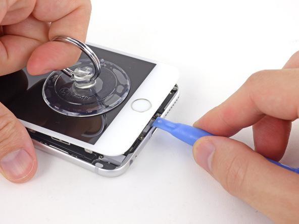 آیفون 6 پلاس تعمیری را روی میز کارتان قرار دهید و با نوک قاب باز کن (مثل عکس ) لبه زیرین درب پشت گوشی را نگه دارید. ساکشن کاپ را با دست دیگرتان به سمت بالا بکشید و سعی کنید که تمرکز نیرو روی لبه زیرین قاب گوشی معطوف باشد. شدت نیروی کششی را به تدریج تا جایی افزایش دهید که شکاف باریکی در لبه زیرین قاب آیفون 6 پلاس ایجاد شود.