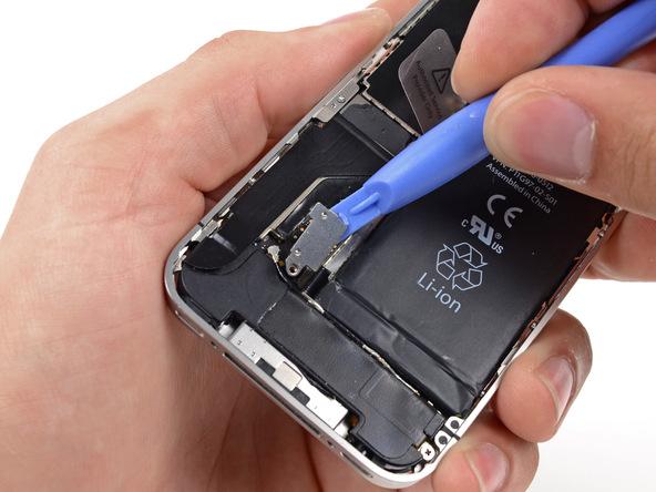 نوک قاب باز کن پلاستیکی یا اسپاتول را از بالا به زیر براکت روی کانکتور باتری آیفون 4 فرو برده و خیلی آرام این براکت را به سمت بالا هول دهید تا از روی کانکتور باتری آزاد شود.