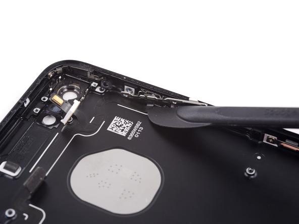 در کنار ماژول دکمه پاور که در مرحله قبل آن را از لبه سمت راست آیفون 7 باز کردید، کابل نگهدارنده دکمه های پاور و تنظیم صدای گوشی چسبانده شده است. نوک هالبرد اسپاجر را دقیقا مثل عکس های ضمیمه شده در زیر این قسمت از کابل مذکور فرو کنید و به تدریج آن را در زیر کابل که بر روی پنل پشتی چسبانده شده حرکت دهید.
