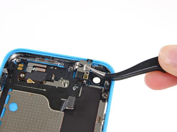 براکت گوشه درب پشت آیفون 5C تعمیری را با نوک پنس گرفته و در مکان امنی قرار دهید که گم نشود.