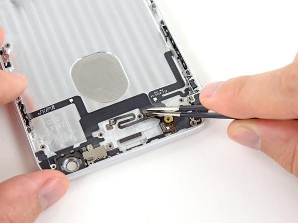 با نوک پنس کاوری که روی کانکتور فلزی دکمه پاور آیفون تعمیری واقع شده را از روی آن جدا نمایید.