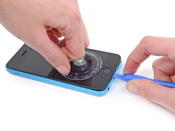 آیفون 5 سی تعمیری را روی یک سطح صاف مثل میز کار قرار دهید و با نوک قاب باز کن پلاستیکی لبه زیرین درب پشت گوشی را مثل عکس اول به سمت پایین فشار دهید تا از روی میز بلند نشود.