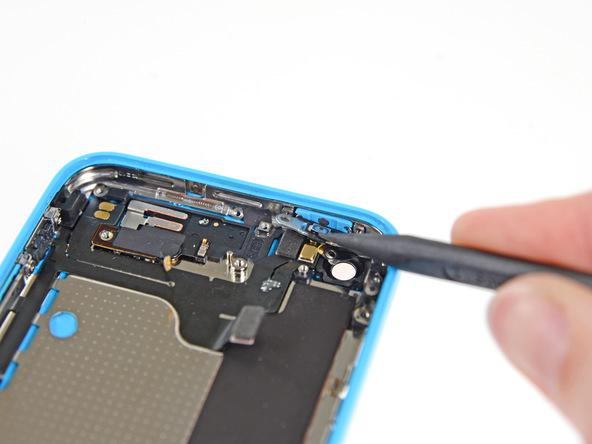 با نوک پنس یا اسپاتول، براکت پشت دکمه پاور آیفون 5C را به سمت پایین فشار دهید تا از مسیر دکمه پاور خارج شود.