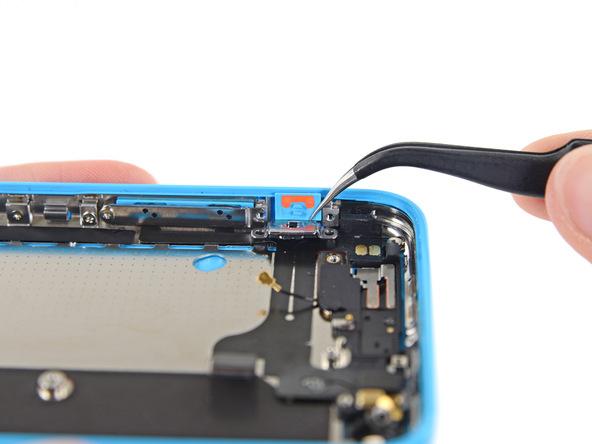کلیپس پشت براکت دکمه سایلنت آیفون 5C را با نوک پنس از لبه درب پشت گوشی جدا کنید.