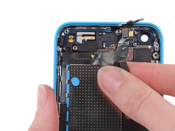 به آرامی لبه سیم دکمه پاور آیفون 5C را با انگشت گرفته و سعی کنید بخش میانی این سیم را هم از روی درب پشت گوشی آزاد نمایید. بعد از آزاد کردن بخش میانی سیم مذکور، آن را کمی به سمت چپ بکشید تا براکت دکمه ولوم گوشی هم از لبه سمت چپ درب پشت آیفون 5C آزاد شود.