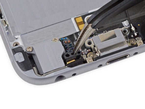 کلیپس نگهدارنده میکروفون آیفون را از لبه زیرین درب پشت گوشی جدا نمایید.
