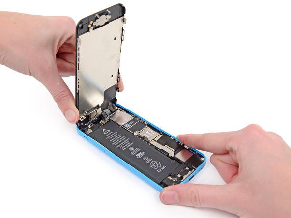 آیفون 5C تعمیری را روی میز کار قرار داده و درب جلو یا همان صفحه نمایش آن را به صورت کتابی از لبه زیرین باز کنید. دقت کنید که به لبه فوقانی قاب آیفون هیچ نیروی کششی اعمال نشود. به محض اینکه درب جلوی آیفون نسبت به قاب پشت گوشی زاویه 90 درجه پیدا کرد، آن را با کش یا به جعبه یا هر ابزار دیگری که میتواند نقش تکیهگاه را ایفاء کند وصل نمایید.