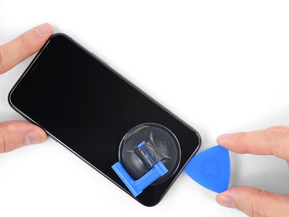 خیلی آرام پیک را دوباره به لبه زیرین قاب آیفون ایکس (iPhone X) فرو برده و از آن جا به سمت لبه راست آن هدایت کنید. پیک را در لبه سمت راست قاب گوشی به صورت رفت و برگشت حرکت دهید تا این قسمت از قاب گوشی هم شل شود.