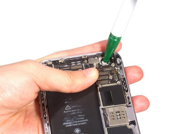 با نوک پنس یا هر ابزار مناسب دیگری شیشه لنز دوربین اصلی آیفون 6 را به سمت خارج پنل هول داده و آن را کاملا از درب پشت گوشی جدا کنید.