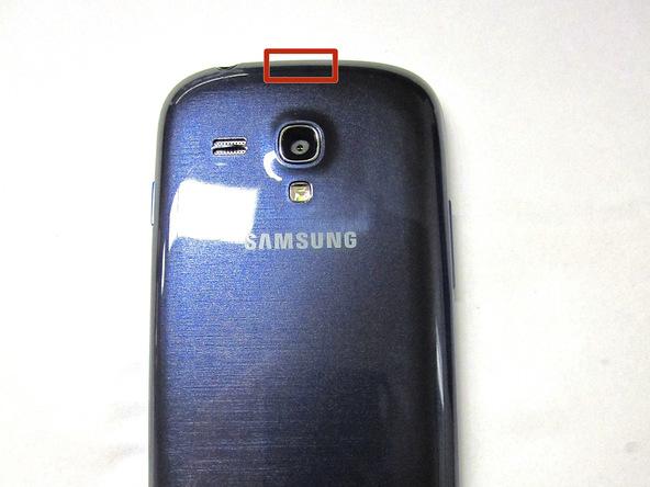 نوک انگشت خود یا نوک قاب باز کن را در زائدهای قرار دهید که روی بخش فوقانی درب پشت Galaxy S3 Mini واقع شده است.