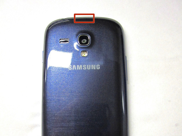 با قرار دادن نوک قاب باز کن در شیار روی لبه فوقانی درب پشت Galaxy S3 Mini و کشیدن آن به سمت عقب، درب پشت گوشی را باز کنید و از گوشی جدا نمایید.