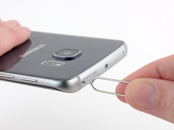 سوزن باز کننده خشاب سیم کارت گلکسی S6 Edge را در مجرای باریکی فرو کنید که روی لبه فوقانی قاب این گوشی موجود است.