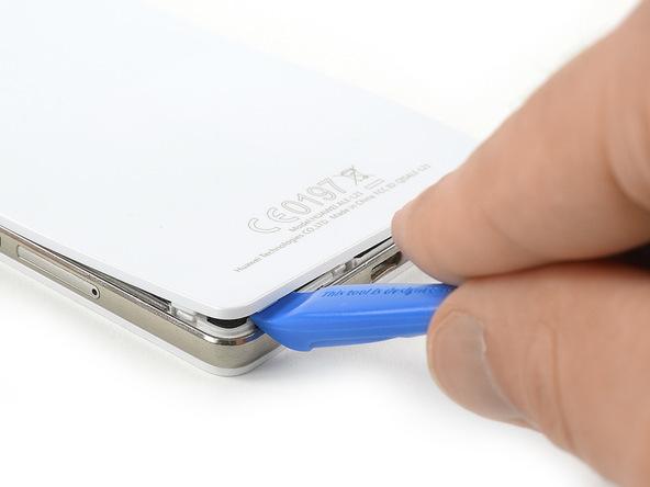 نوک قاب باز کن پلاستیکی را به آرامی از لبه زیرین قاب هوآوی P9 Lite به داخل شکاف مابین درب پشت و بدنه اصلی گوشی فرو ببرید و خیلی آرام سعی کنید لبه زیرین درب پشت گوشی را با نوک اسپاتول شل نمایید.