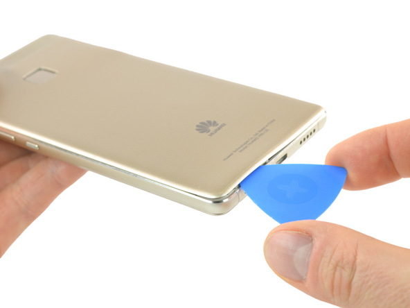 نوک پیک را به آرامی از لبه زیرین قاب گوشی به داخل شکاف مابین بدنه و درب پشت هوآوی P9 Lite (پی 9 لایت) فرو ببرید.