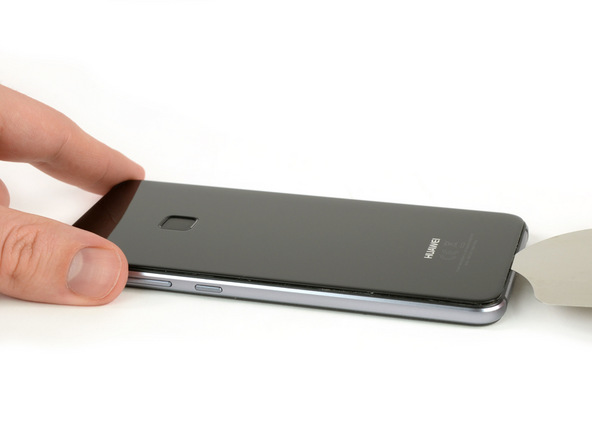 نوک پیک را به آرامی در لبه زیرین قاب هوآوی پی 10 لایت (P10 Lite) فرو ببرید. برای انجام این کار میتوانید از ساکشن کاپ کمک بگیرید یا با سشوار یا آیاوپنر به لیه زیرین قاب آن گرما بدهید. پس از وارد کردن نوک پیک، آن را در لبه زیرین قاب گوشی حرکت دهید تا این بخش از قاب هوآوی پی 10 لایت کاملا شل شود.