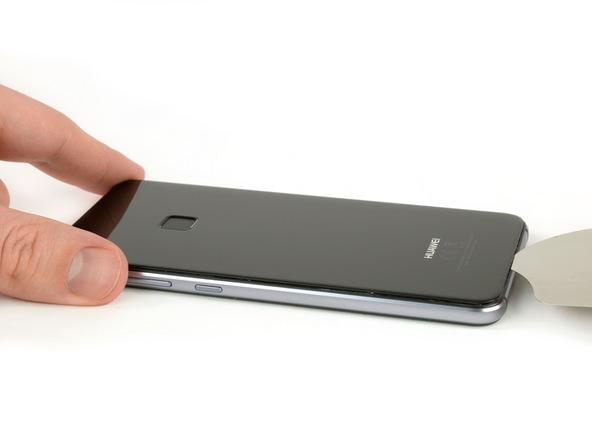 نوک پیک را به آرامی از لبه زیرین به داخل شکاف مابین درب پشت گوشی و بدنه آن فرو ببرید. میتوانید برای انجام این کار از ساکشن کاپ هم کمک بگیرید. همچنین گرما دادن به لبه زیرین درب پشت هوآوی پی 10 لایت هم میتواند روش خوبی برای ساده تر شدن این مرحله باشد. بعد از اینکه نوک پیک از لبه تحتانی به داخل شکاف مابین درب پشت و بدنه گوشی فرو برده شد، پیک را در این قسمت به صورت رفت و برگشت حرکت دهید تا لبه زیرین درب پشت گوشی شل شود.