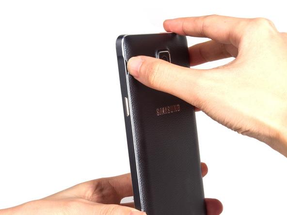 گلکسی نوت 4 تعمیری را خاموش کرده و درب پشت آن از بدنه گوشی جدا کنید. بدین منظور میتوانید از ناخن انگشت خود یا ابزاری مثل اسپاتول استفاده کنید.