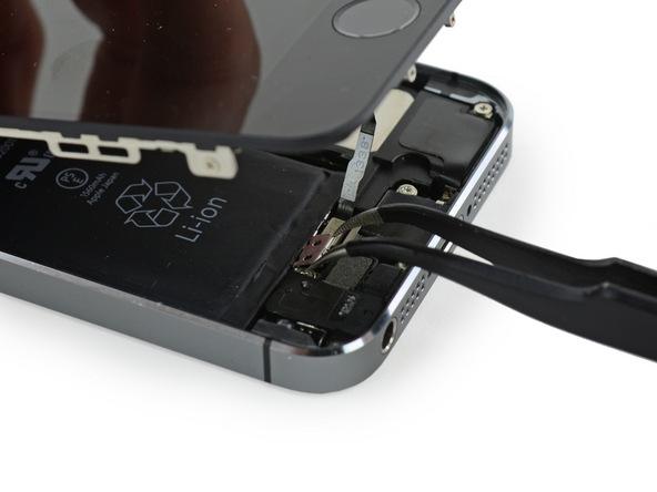 بعد از تعویض دکمه ولوم آیفون 5S (تنظیم صدا) و زمانی که نوبت به جا زدن براکت دکمه هوم گوشی میرسد باید ابتدا براکت مذکور را مثل عکس با پنس بگیرید. پنس باید لبه های عرضی براکت را نگه داشته و لبه طولی دورتر براکت رو به سمت پایین شیب داده شود.