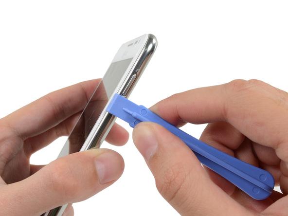 نوک قاب باز کن پلاستیکی را از کنار دکمه پاور گلکسی نوت تعمیری به داخل شکاف مابین فریم میانی و پنل جلوی گوشی فرو ببرید.
