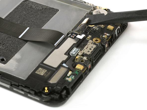 با نوک اسپاتول سر صاف دو کانکتور اسپیکر و فلت شارژ را از روی برد ثانویه هوآوی میت 9 تعمیری آزاد کنید.